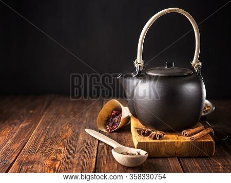 Black Ceramic Teapot With Tea, Different Tea And Herbs , On Wooden Background.