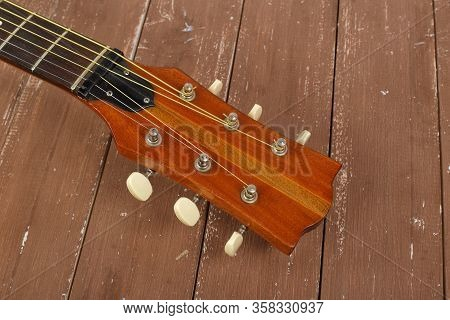 Musical Instrument - Headstock Peghead Acoustic Guitar On A Wood Background.
