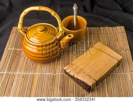 Chinese Pressed Pu-erh Tea In Bamboo Leaf Packaging And Tea Accessories, Close-up, Macro