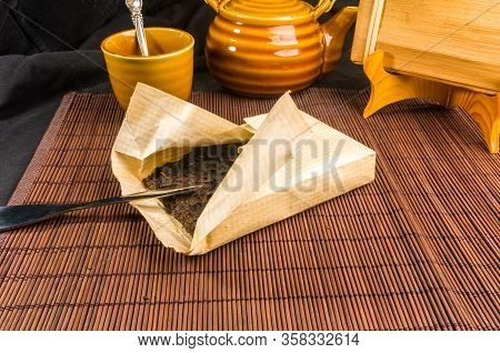 Chinese Pressed Pu-erh Tea On Wrapping Paper And Tea Accessories, Close-up, Macro
