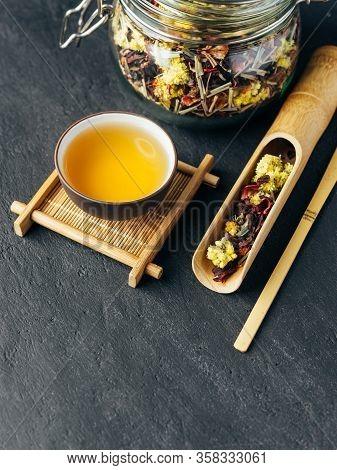 Freshly Brewed Herbal Tea. Wooden Spoon. Glass Jar With Tea Leaves.dark Concrete Stone Background.