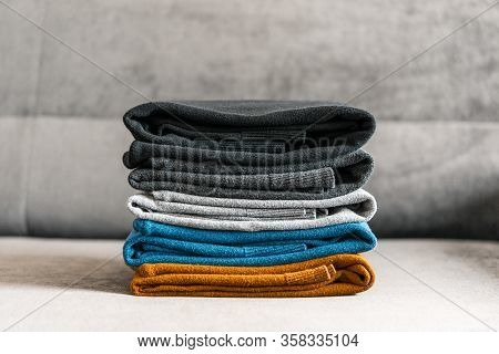 Pile Of Sweaters On The Gray Couch. Mens Textile Clothing.