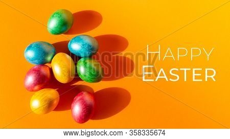 Colorful Easter Eggs On Orange Background. Happy Easter Composition. Copy Space.