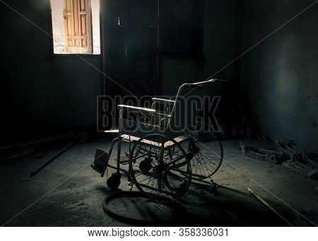 An Abandoned Old Wheelchair In The Old Room