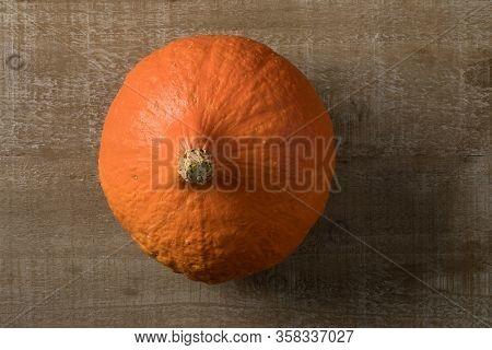 Fresh orange Hokkaido pumpkin close up seen from above on a wooden background