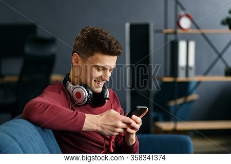 Enjoy Listening To Music.young Man In Headphones Listening Music On Smart Phone Using Music App. Por