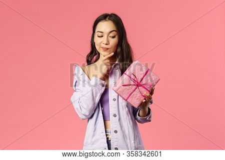 Portrait Of Curious Enthusiastic Young Asian Girl Peeking At Wrapped Box, Smirk And Touching Jaw As