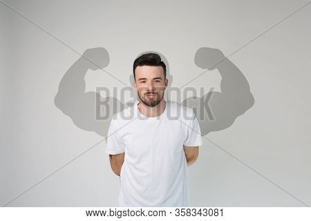 Young Man Isolated Over Background. Guy In White Shirt Posing On Camera. Shade Of Muscular Powerful