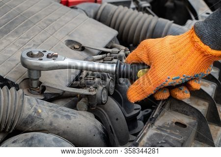 Male Auto Mechanic Unscrews The Nut On The Car Engine With A Wrench