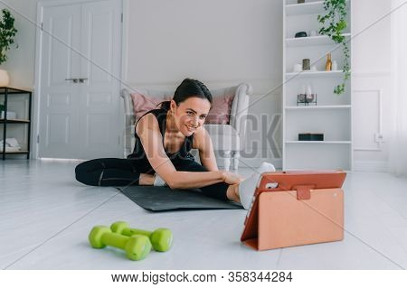 Girl Looking At A Tablet Does Exercises At Home. Pretty Woman Doing Fitness At Home.