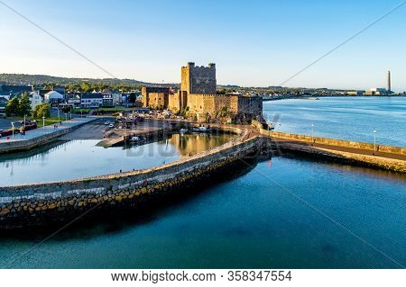 Medieval Norman Castle And Harbor With Boat Ramp And Wave Breaker In Carrickfergus Near Belfast, Nor