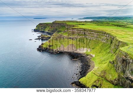 Northern Ireland, Uk. Cliffs At Atlantic Coast In County Antrim With Visible Geological Strata, And