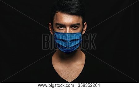 Portrait Of Handsome Man Wearing Medical Blue Mask On The Face During Virus Epidemic Lockdown Posing