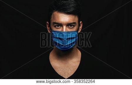 Portrait Of Handsome Man Wearing Medical Blue Mask On The Face During Virus Epidemic Lockdown Posing