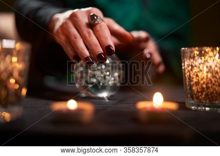 Close-up of fortuneteller divining on magic ball at table with burning candles