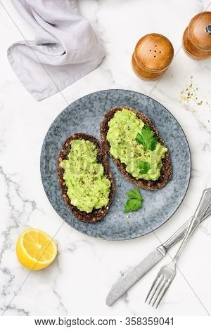Rye Bread Toast With Mashed Avocado Cream. Vegan Avocado Toast With Hemp Seeds