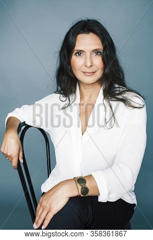 Pretty Brunette Confident Mature Woman Sitting On Chair In Studio, Lifestyle People Concept