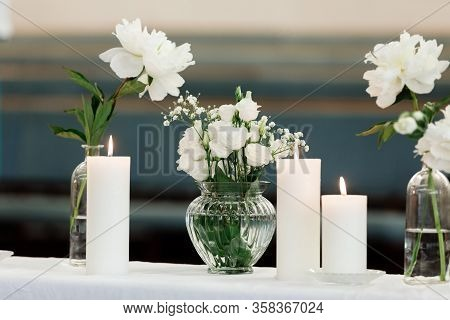 White Flowers And Candles Decoration For A Wedding. Flowers Composition. White Candles On White Tabl