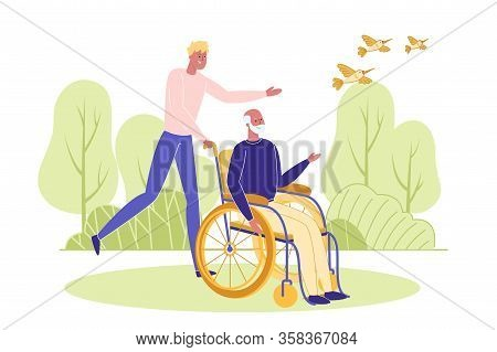 Young Man Assists Elderly Handicapped Person To Move On Wheelchair During Walk. Social Worker, Volun