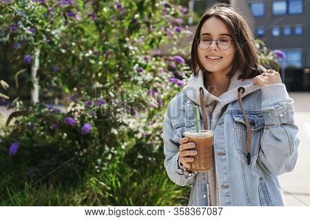 Portrait Of Young Attractive Woman Standing On Street Near Green Bushes, Drinking Favorite Coffee, I