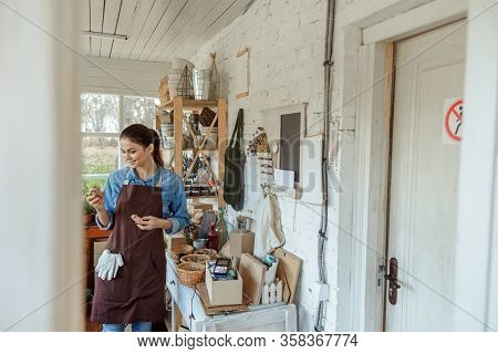 Pleased Female Herbalist With Vials Standing Indoors