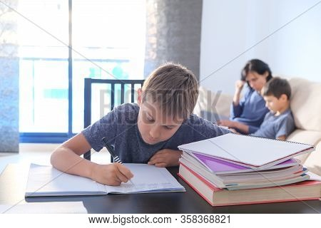 Children Doing Homework At Home. Mother Helping Her Son With Homework And Works Online With Laptop C