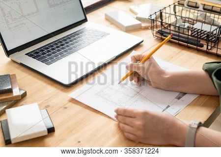 Hand of young female architect with pencil over peper with sketch of house during work over new project in front of laptop