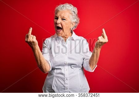 Senior beautiful woman wearing elegant shirt standing over isolated red background Showing middle finger doing fuck you bad expression, provocation and rude attitude. Screaming excited