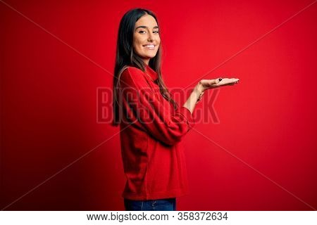 Young beautiful brunette woman wearing casual sweater over isolated red background pointing aside with hands open palms showing copy space, presenting advertisement smiling excited happy