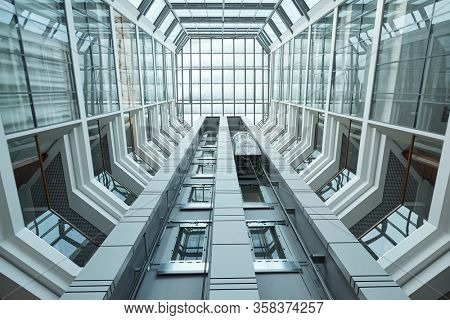 Below view of design of contemporary business center interior surrounded by walls and windows and moving elevator