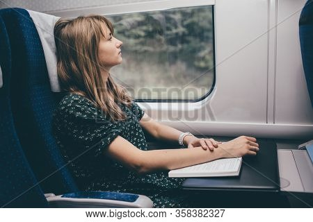Young Woman Travel In Train. Sitting Alone And Look At Window. Relax After Reading Book Or Studying.