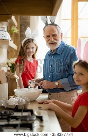 Mirthful Man Cracking Eggs And Smiling Stock Photo