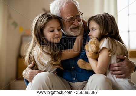 Mirthful Children Hugging Their Grandpa Stock Photo