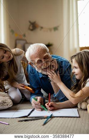 Twin Girls Having Fun With Mirthful Grandfather Stock Photo