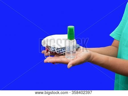 Bottle Gel Alcohol And Mask Fabric Prophylaxis Virus Homemade Pile On Hand Over Blue Background. Pre