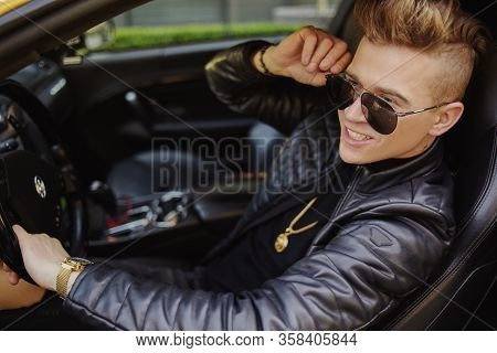 A Businessman Is Sitting In A Golden Car. A Man Is Driving Inside A Car. Driver. Chic Man With Glass