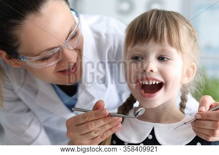 Woman Dentist Examines Teeth In Clinic At Child. Doctor Will Monitor Home Dental Hygiene. Dentist Wi