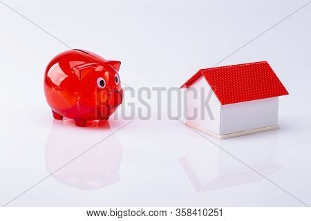 The Photo Shows A Red Piggy Bank With A Model House, Isolated On A White Background