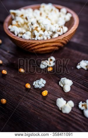 Popcorn In Wood Dish Or Bowl On Dark Wood Table