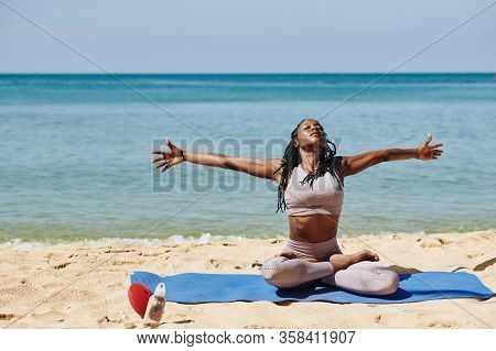 Fit Black Young Woman Sitting In Lotus Position, Outstretching Arms And Squeezing Shoulder Blades To