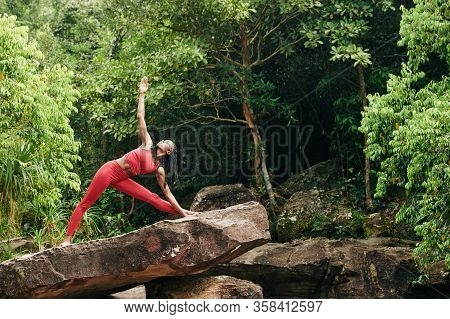 Pretty Fit Black Woman Doing Triangle Pose On Big Rock In The Forest
