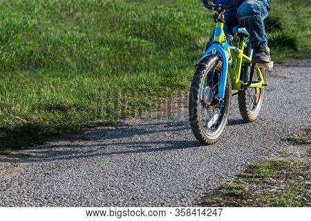 A Child Rides A Bicycle Along The Path, Among The Green Grass In The Sun. Close-up On Wheels And Ped