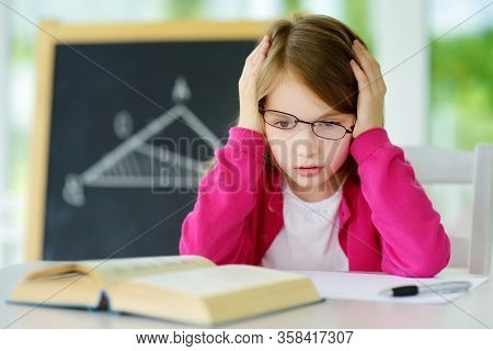 Stressed Schoolgirl Studying With A Pile Of Books On Her Desk. Young Girl Doing Her Homework. Educat
