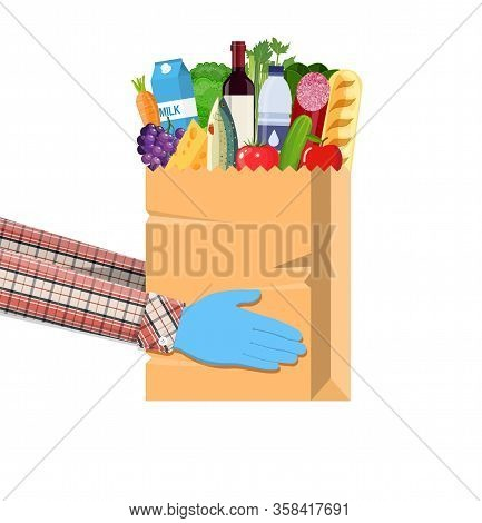 Hands Hold Paper Shopping Bag Full Of Groceries Products With Rubber Gloves. Grocery Store. Supermar