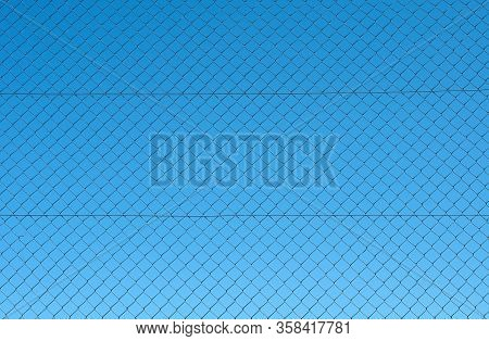 View To Clear Blue Sky Through The Net Of A Metal Chain Link Fence