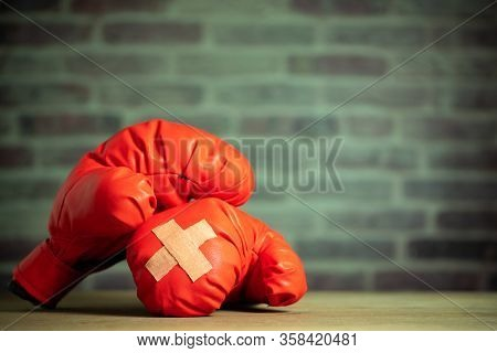 Red Boxing Gloves On Wooden Table And Brick Wall At The Sport Gym. Adhesive Plaster Across Each Othe