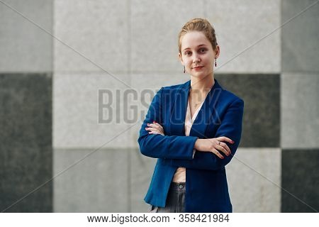 Portrait Of Young Beautiful Business Lady Looking At Camera And Folding Arms To Express Confidence