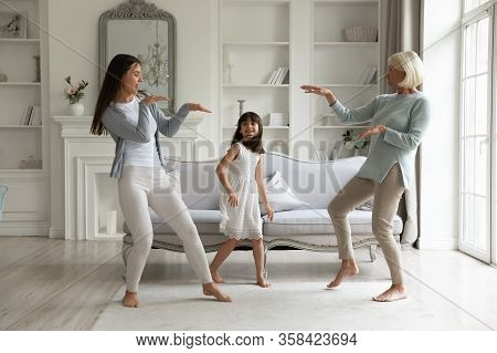 Happy Three Generations Of Women Dancing Together