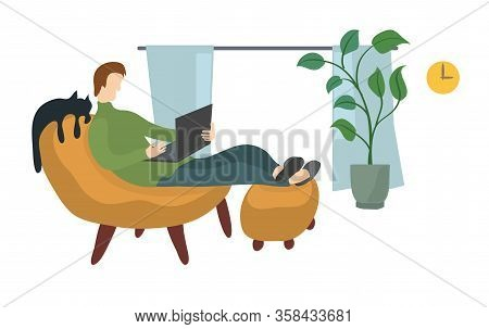 A Man In An Upholstered Chair Works With A Laptop In A Home Environment. Comfortable Remote Work