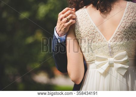 Man And Woman Hug While Walking In The Park On A Sunny Day After The Registration Of Marriage. Happy